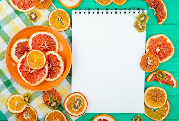 Vue de dessus d'un carnet de croquis avec des tranches d'orange et de pamplemousse séchées sur une plaque et des kiwis séchés sur fond de bois vert