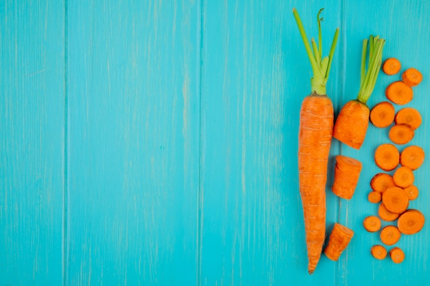 Vue de dessus des carottes coupées entières coupées sur le côté droit et fond bleu avec copie espace