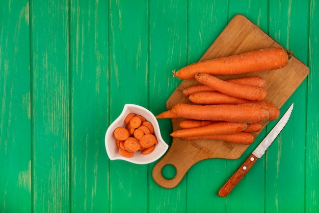 Vue de dessus des carottes fraîches sur une planche de cuisine en bois avec un couteau sur un mur en bois vert avec espace copie