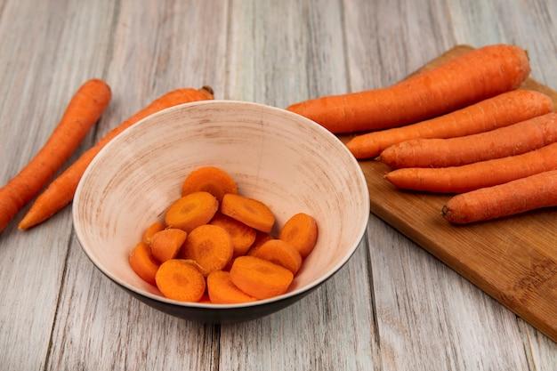 Vue de dessus des carottes hachées orange sur un bol avec des carottes sur une planche de cuisine en bois sur un mur en bois gris