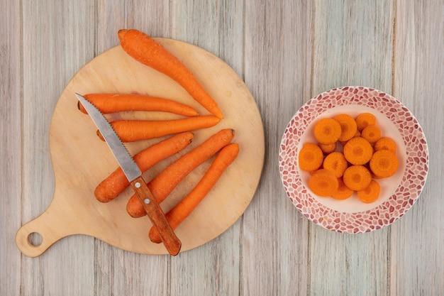 Vue de dessus des carottes orange sur une planche de cuisine en bois avec un couteau avec des carottes hachées sur un bol sur un fond en bois gris