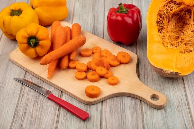 Vue de dessus des carottes à peau orange sur une planche de cuisine en bois avec un couteau avec des poivrons colorés isolés sur un fond en bois gris