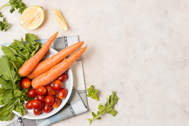 Vue de dessus de carottes et tomates sur plaque