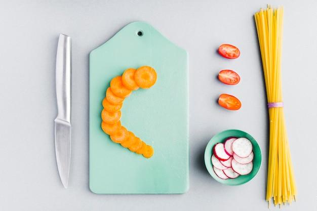 Vue de dessus des carottes en tranches sur une planche à découper avec des spaghettis non cuits