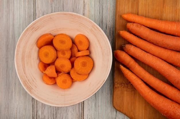 Vue de dessus de carottes très nutritives sur une planche de cuisine en bois avec des carottes hachées sur un bol sur un mur en bois gris