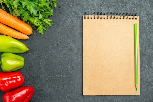 Vue de dessus des carottes vertes et poivrons sur le côté gauche avec bloc-notes sur le côté sur la table gris foncé