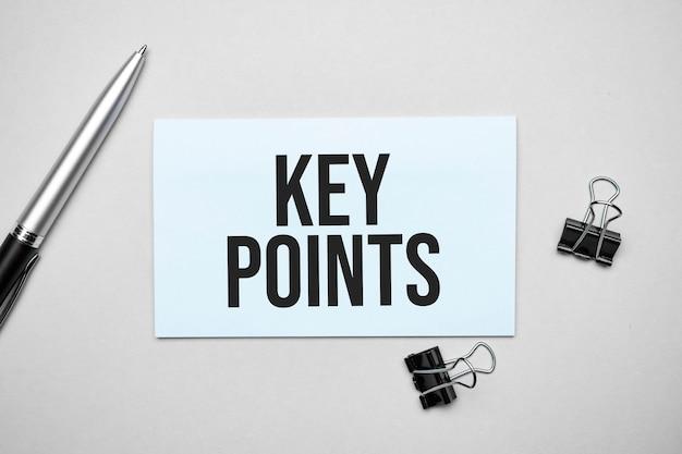 Vue de dessus d'une carte de visite avec texte points clés, stylo, trombones sur une surface colorée