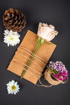 Vue de dessus de carte de voeux en papier brun et rose de couleur blanche attachée avec une corde et un œillet turc avec des fleurs de marguerite et des cônes sur tableau noir