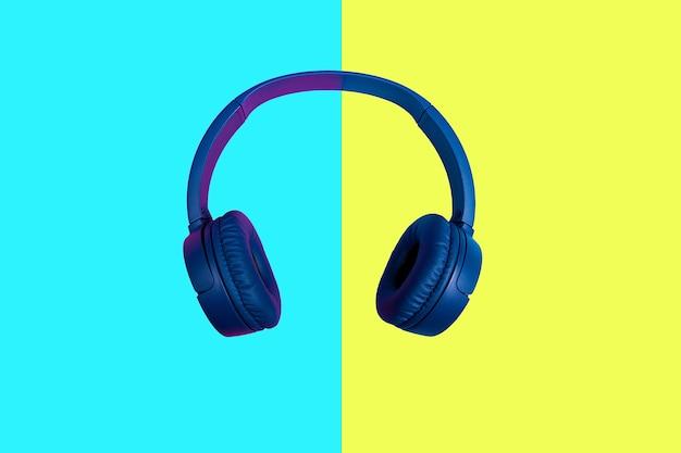 Vue de dessus sur un casque sans fil bleu sur fond de couleur vive. style plat minimal. design et couleurs