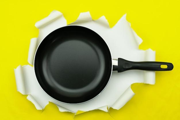 Vue de dessus de la casserole d'ustensiles de cuisine sur papier déchiré jaune.