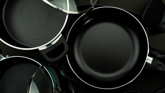 Vue de dessus de la casserole d'ustensiles de cuisine et pot sur cuir noir.