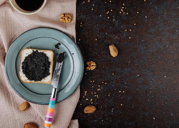 Vue de dessus caviar noir pain grillé pain blanc avec du fromage cottage caviar noir amande noix sur la gauche et copie espace sur fond noir