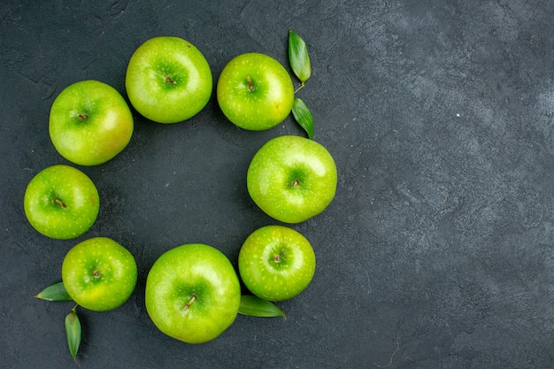 Vue de dessus cercle rangée pommes vertes sur l'espace de copie de table sombre