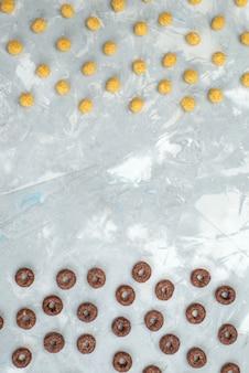 Vue de dessus des céréales au chocolat bordées de céréales jaunes sur gris