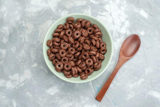 Vue de dessus des céréales au chocolat à l'intérieur de la plaque verte avec du bois, cuillère sur bleu, céréales pour petit déjeuner cornflakes cacao