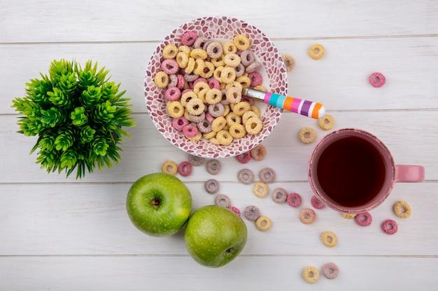 Vue de dessus des céréales colorées sur bol avec cuillère colorée avec une tasse de thé aux pommes vertes sur blanc