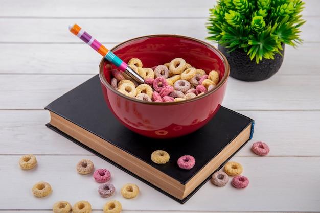 Vue de dessus des céréales colorées sur bol rouge avec cuillère colorée avec céréales isolated on white