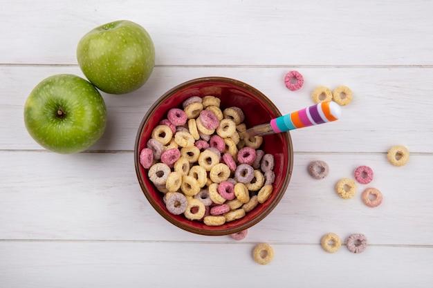 Vue de dessus des céréales colorées sur bol rouge avec cuillère avec pommes vertes sur blanc