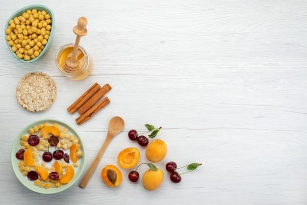 Vue de dessus des céréales avec du lait à l'intérieur de la plaque avec des craquelins fruits à la cannelle et du miel sur blanc, boire le petit déjeuner de crémerie lait