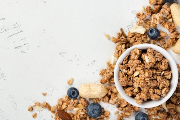 Vue de dessus des céréales du petit déjeuner dans un bol avec des noix et des bleuets