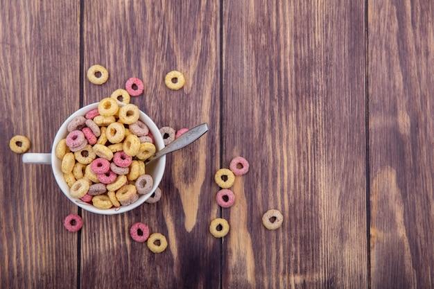 Vue de dessus des céréales multicolores sur un bol avec une cuillère avec des céréales isolé sur une surface en bois