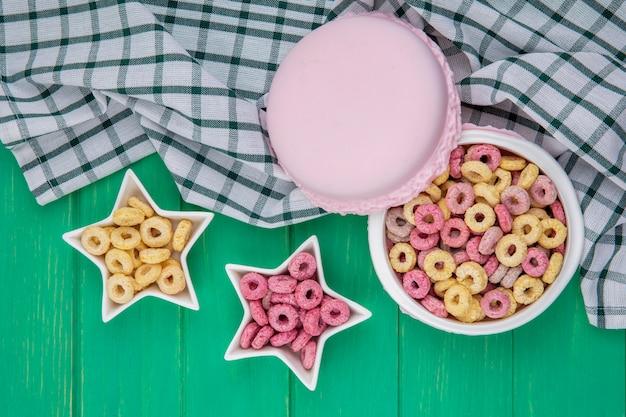Vue de dessus des céréales multicolores sur un bol sur nappe à carreaux sur surface verte
