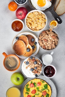 Vue de dessus des céréales avec omelette et crêpes pour le petit déjeuner