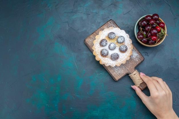 Vue de dessus des cerises aigres fraîches avec gâteau rond sur un bureau sombre, biscuit gâteau aux fruits sucré