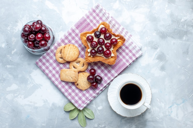 Vue de dessus des cerises aigres fraîches à l'intérieur de la plaque avec gâteau crémeux en forme d'étoile et biscuits sur un bureau blanc, biscuit gâteau d'été aux fruits