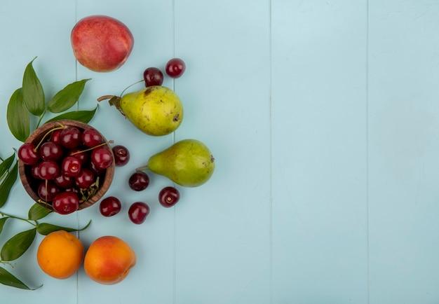 Vue de dessus des cerises dans un bol et motif de poires abricots cerises de pêche avec des feuilles sur fond bleu avec copie espace