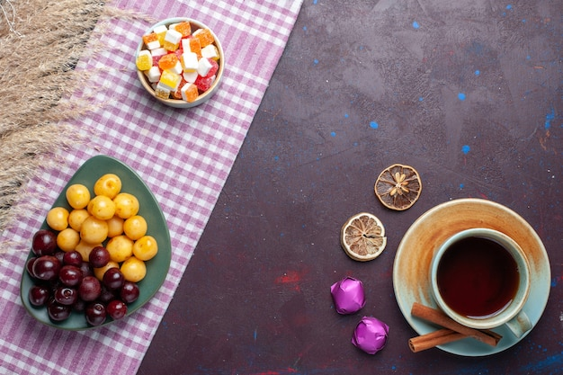 Vue de dessus des cerises douces fraîches à l'intérieur de la plaque avec du thé à la cannelle et des bonbons sur le sol noir fruits frais doux et mûr santé d'été sucré sucre