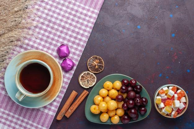 Vue de dessus des cerises douces fraîches à l'intérieur de la plaque avec du thé à la cannelle et des bonbons sur la surface sombre