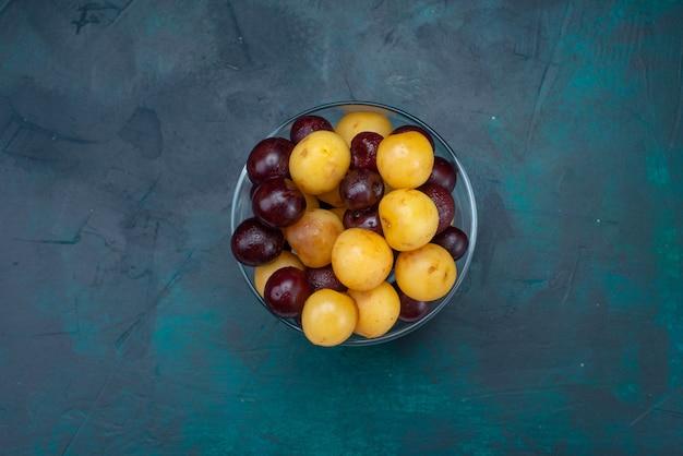 Vue de dessus cerises fraîches fruits moelleux à l'intérieur du verre sur le fond bleu foncé cerise douce cerise mûre