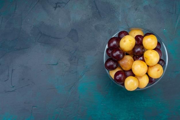 Vue de dessus cerises fraîches fruits moelleux à l'intérieur du verre sur le fond bleu foncé cerise fraîche cerise douce vitamine mûre