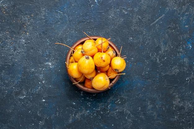 Vue de dessus des cerises jaunes fraîches fruits mûrs et sucrés sur sombre, baies de fruits frais moelleux