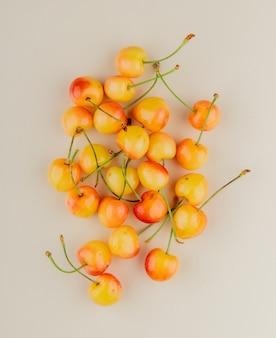 Vue de dessus des cerises jaunes sur une surface blanche