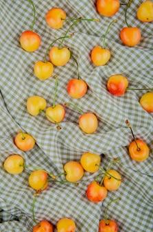 Vue de dessus des cerises jaunes sur une table en tissu à carreaux