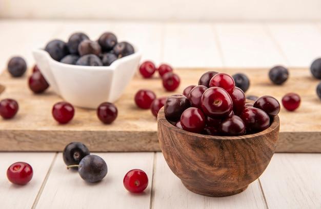 Vue de dessus des cerises rouges sur un bol en bois avec des prunelles sur un bol blanc sur une planche de cuisine en bois sur fond blanc