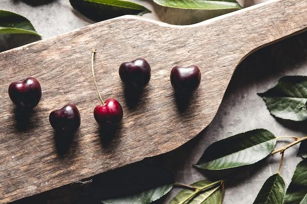 Vue de dessus des cerises rouges sur un bol avec des tranches de pêches sur une planche de cuisine en bois avec un couteau sur un béton
