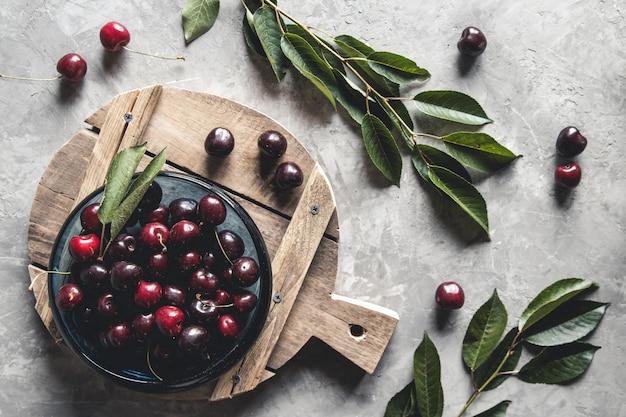 Vue de dessus des cerises rouges sur un bol avec des tranches de pêches sur une planche de cuisine en bois avec un couteau sur un fond de béton