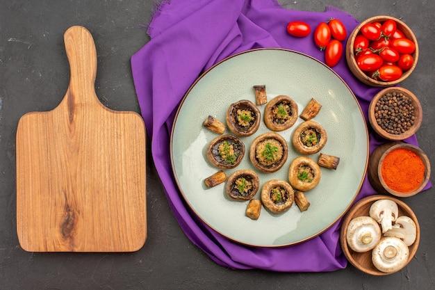 Vue de dessus des champignons cuits à l'intérieur de la plaque avec des assaisonnements sur un plat de tissu violet repas champignons dîner cuisson