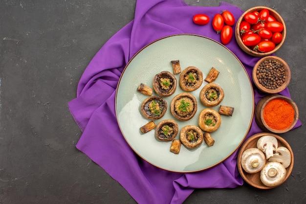 Vue de dessus des champignons cuits à l'intérieur de la plaque avec des assaisonnements sur le plat de tissu violet repas cuisson dîner aux champignons