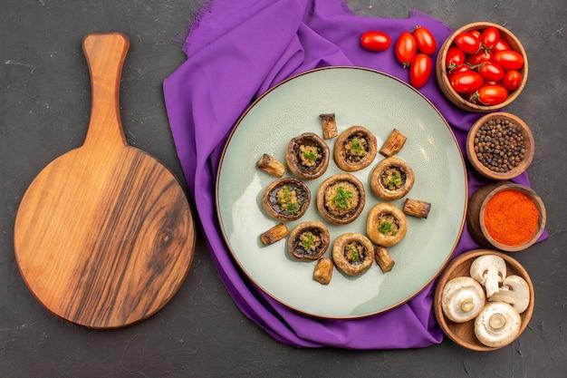 Vue de dessus des champignons cuits à l'intérieur de la plaque avec des assaisonnements sur le plat de tissu violet repas dîner aux champignons cuisson