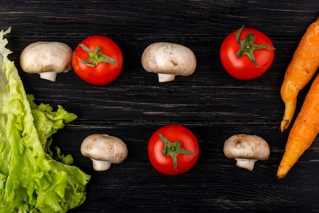 Vue de dessus de champignons frais champignon et tomates à la carotte sur fond de bois foncé