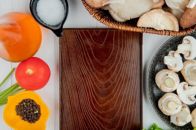 Vue de dessus de champignons frais dans un panier en osier et bouteille de tomate d'huile d'olive sel et grains de poivre disposés autour de la planche de bois sur blanc