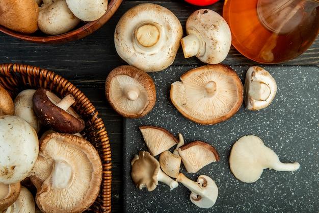 Vue de dessus des champignons frais dans un panier en osier et sur une planche à découper noire sur bois foncé