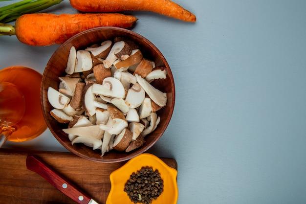 Vue de dessus de champignons frais tranchés dans un bol et un couteau de cuisine avec des grains de poivre noir sur une planche à découper en bois et des carottes fraîches sur bleu clair avec copie espace