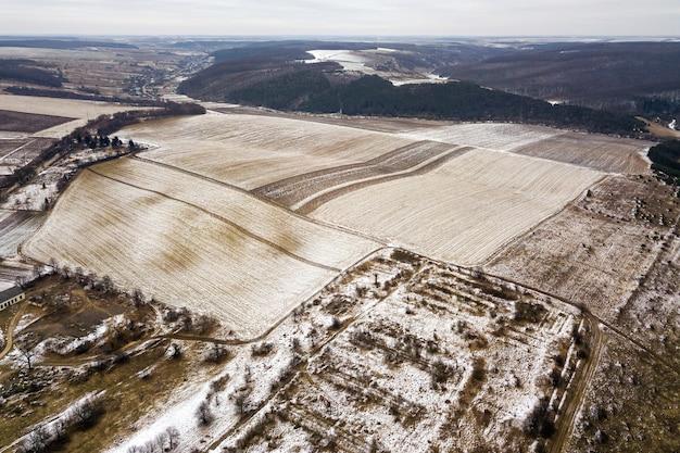 Vue de dessus des champs enneigés vides et des collines boisées sur ciel nuageux
