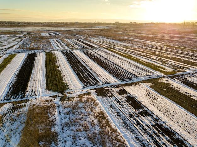Vue de dessus des champs enneigés vides patchés paysage