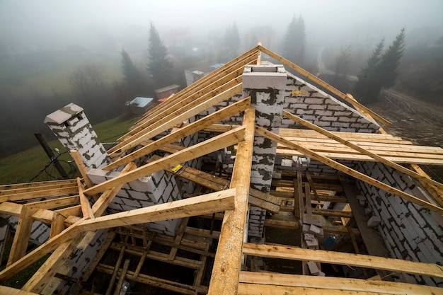 Vue de dessus de la charpente de toit à partir de poutres en bois et de planches sur des murs en blocs isolants en mousse creuse.